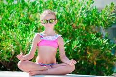 Portret van aanbiddelijk meisje in yoga openlucht op vakantie stock afbeeldingen