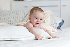 Portret van aanbiddelijke 9 van de babymaanden oud jongen die op groot hoofdkussen op bed liggen Stock Fotografie