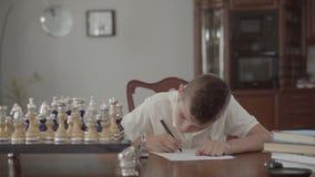 Portret van aanbiddelijke nadenkende kerelzitting bij de lijst thuis De jongen daagde en schrijvend iets op een stuk van stock video