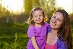 Portret van aantrekkelijk blondemeisje en haar moeder het omhelzen bekijkend camera en in openlucht glimlachend stock afbeeldingen