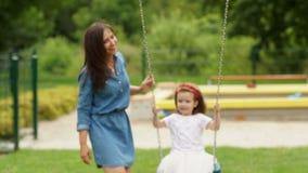 Portret van Aantrekkelijk Brunette en Haar Leuke Dochter die op de Speelplaats spelen Meisje die een Schommeling in openlucht ber stock videobeelden