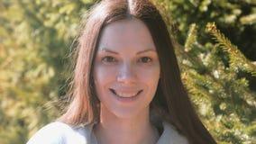 Portret van aantrekkelijk het glimlachen jong vrouwenbrunette in stadspark stock videobeelden