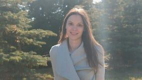 Portret van aantrekkelijk het glimlachen jong vrouwenbrunette in stadspark stock video