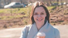 Portret van aantrekkelijk het glimlachen jong vrouwenbrunette in stadspark met koffie stock videobeelden
