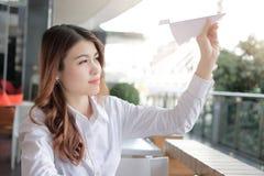 Portret van aantrekkelijk jong Aziatisch het document van de onderneemsterholding vliegtuig in haar hand op kantoor Bedrijfs visi Royalty-vrije Stock Foto's