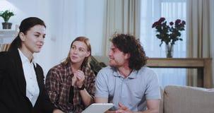 Portret van aantrekkelijk jong paar die met hun makelaar in onroerend goed op de bank babbelen hebben zij het bespreken over huis stock videobeelden
