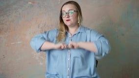 Portret van aantrekkelijk plus grootte in glazenvrouw die die emotiespositief, vreugde en verrassing hebben over gekleurde achter stock footage