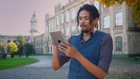Portret van aantrekkelijke Afrikaans-Amerikaanse student met dreadlocks die zorgvuldig met tablet aan universiteit werken stock videobeelden