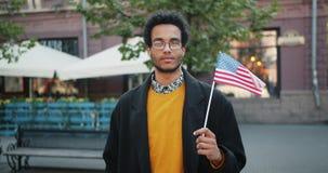 Portret van aantrekkelijke Afrikaanse Amerikaanse student die de openluchtvlag van de holdingsv.s. bevinden zich stock videobeelden