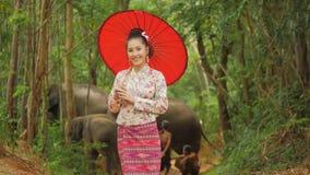 Portret van aantrekkelijke Aziatische vrouw die in traditioneel zuidoostaziatisch kostuum aan camera glimlachen stock videobeelden