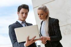 Jonge partners die gegevens over laptop herzien. stock foto's