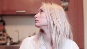 Portret van aantrekkelijke blondevrouw die met ongerust gemaakt gezicht rond en omhoog kijken stock video