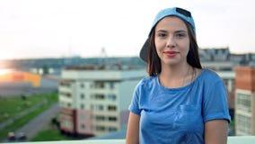 Portret van aantrekkelijke glimlachende jonge tienervrouw in GLB wat betreft haar haar openlucht stock video