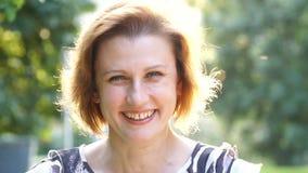 Portret van Aantrekkelijke Glimlachende Kaukasische het Behoren tot een bepaald ras Jonge Vrouw in het park stock videobeelden