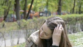 Portret van aantrekkelijke glimlachende Kaukasische het behoren tot een bepaald ras jonge vrouw in stadspark stock videobeelden