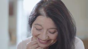 Portret van aantrekkelijke hogere vrouw die met schitterend lang donker haar en prettige brede glimlach in camera binnen dicht ki stock footage