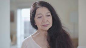 Portret van aantrekkelijke hogere vrouw die met schitterend lang donker haar rond met zachte prettige binnen dicht glimlach kijke stock video
