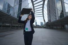 Portret van aantrekkelijke jonge Aziatische bedrijfsvrouw die en documentomslag lopen opheffen bij stoep van stedelijke stadsacht royalty-vrije stock afbeelding