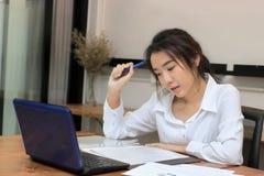 Portret van aantrekkelijke jonge Aziatische onderneemster die aan de werkplaats in bureau werken Het denken en nadenkend bedrijfs Stock Afbeeldingen
