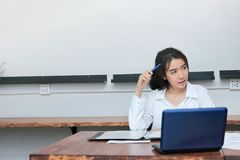 Portret van aantrekkelijke jonge Aziatische onderneemster die aan de werkplaats in bureau werken Het denken en nadenkend bedrijfs Stock Afbeelding