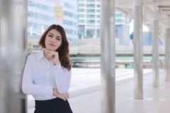 Portret van aantrekkelijke jonge Aziatische onderneemster die een pool leunen en aan camera bij gang buiten bureau met exemplaarr Royalty-vrije Stock Afbeeldingen