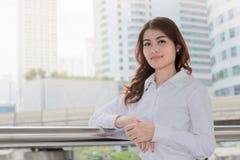 Portret van aantrekkelijke jonge Aziatische onderneemster die op camera de stedelijke bouw met zonneschijneffect achtergrond beki Stock Afbeelding