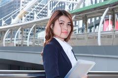 Portret van aantrekkelijke jonge Aziatische secretaressevrouw met ringsbindmiddel die zich op buitenkantoor bevinden Royalty-vrije Stock Afbeelding