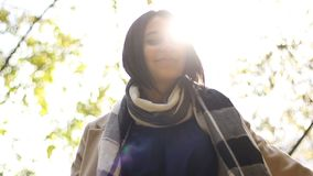 Portret van aantrekkelijke jonge donkerbruine glimlachenvrouw bij zonsondergang bij het park stock video