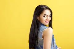 Portret van aantrekkelijke jonge donkerbruine vrouw in denimvest op gele achtergrond stock fotografie