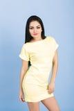Portret van aantrekkelijke jonge donkerbruine vrouw in gele kleding op blauwe achtergrond Royalty-vrije Stock Fotografie