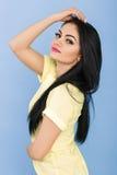 Portret van aantrekkelijke jonge donkerbruine vrouw in gele kleding op blauwe achtergrond Royalty-vrije Stock Afbeeldingen