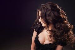 Portret van aantrekkelijke jonge donkerbruine vrouw met luxueuze krullen royalty-vrije stock foto's