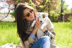Portret van aantrekkelijke jonge vrouw die leuk de terriërpuppy van hefboomrussell in park, groen gazon, gebladerteachtergrond ko Stock Afbeelding
