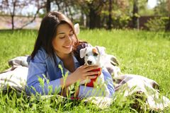 Portret van aantrekkelijke jonge vrouw die leuk de terriërpuppy van hefboomrussell in park, groen gazon, gebladerteachtergrond ko Royalty-vrije Stock Foto