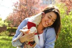 Portret van aantrekkelijke jonge vrouw die leuk de terriërpuppy van hefboomrussell in park, groen gazon, gebladerteachtergrond ko Royalty-vrije Stock Afbeeldingen