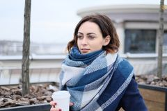 Portret van aantrekkelijke jonge vrouw die sjaal dragen en witte koffiekop op een koude en sneeuw de winterdag houden Royalty-vrije Stock Foto's