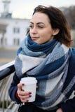 Portret van aantrekkelijke jonge vrouw die sjaal dragen en witte koffiekop op een koude en sneeuw de winterdag houden Stock Afbeelding