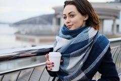 Portret van aantrekkelijke jonge vrouw die sjaal dragen en witte koffiekop op een koude en sneeuw de winterdag houden Stock Foto's