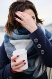 Portret van aantrekkelijke jonge vrouw die sjaal dragen en witte koffiekop op een koude en sneeuw de winterdag houden Stock Foto