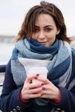 Portret van aantrekkelijke jonge vrouw die sjaal dragen en witte koffiekop op een koude en sneeuw de winterdag houden Royalty-vrije Stock Fotografie