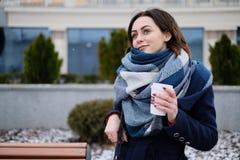 Portret van aantrekkelijke jonge vrouw die sjaal dragen en witte koffiekop op een koude en sneeuw de winterdag houden Stock Afbeeldingen