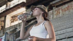 Portret van aantrekkelijke jonge vrouw in het militaire drinkwater van GLB van de fles in de stoffige vuile verlaten bouw stock video