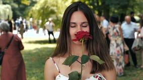 Portret van Aantrekkelijke jonge vrouw met rozen in haar hand bij de gebeurtenis met mensen op achtergrond stock footage