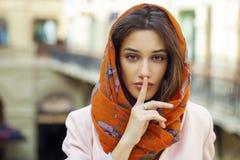 Portret van aantrekkelijke jonge vrouw met vinger op lippen Stock Foto's
