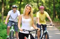 Portret van aantrekkelijke jonge vrouw op fiets en twee mannen erachter Stock Foto's