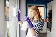 Portret van Aantrekkelijke jonge vrouwen schoonmakende vensters in het huis stock fotografie