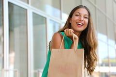 Portret van aantrekkelijke lachende vrouw met klantenzak in haar hand met gloed Het glimlachende meisje die van de schoonheidsman stock fotografie