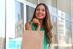Portret van aantrekkelijke lachende vrouw met klantenzak in haar hand met gloed Het glimlachende meisje die van de schoonheidsman royalty-vrije stock afbeelding