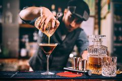Portret van aantrekkelijke professionele barman die alcoholische dranken voorbereiden bij bar stock foto