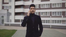 Portret van aantrekkelijke slanke zakenman in formeel kostuum die op smartphone tegen de achtergrond van commercieel centrum spre stock video